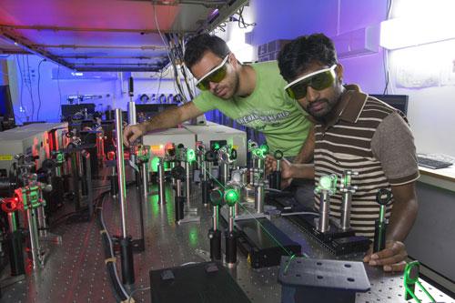 Athanasios Margiolakis and Bala Murali Krishna Mariserla, OIST Posdoctoral researcher, perform an experiment in Femtosecond laser laboratory