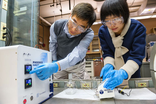 chemical engineer Jie Li, left, and postdoctoral researcher Alina Yan create coated nanoparticles in a continuous flow reactor