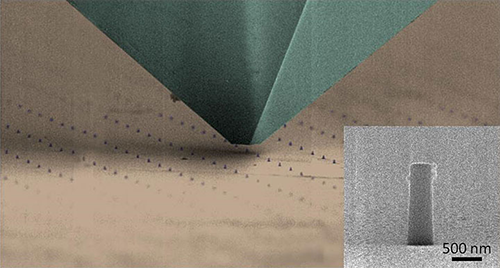 A scanning electron microscope image of a nanomechanical testing tip passing over arrays of hybrid nanopillars