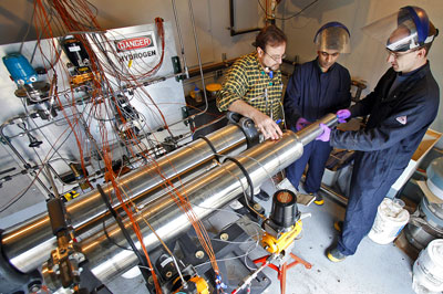 >Issam Mudawar, from left, a Purdue professor of mechanical engineering, discusses a hydrogen-storage system for cars with graduate student Milan Visaria and Timothée Pourpoint, an assistant professor of aeronautics and astronautics and manager of the Hydrogen Systems Laboratory