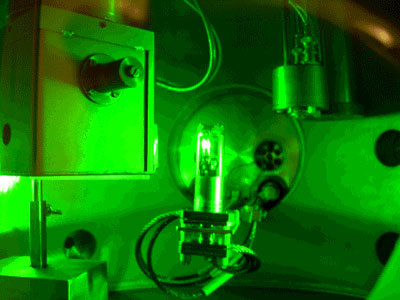 The photograph shows an experiment in which dense deuterium is irradiated by a laser. The white glow in the container in the centre of the photograph is from deuterium