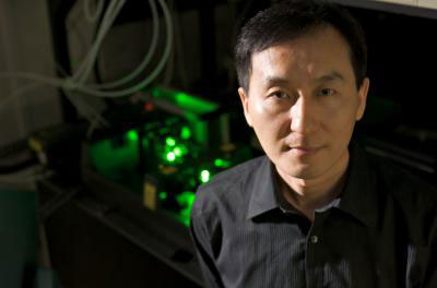 Chunlei Guo uses the femtosecond laser (behind him) to create nanostructures in metal that can move liquid uphill