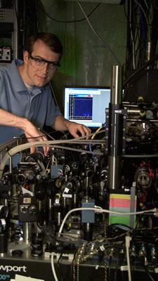 NIST postdoctoral researcher David Hanneke at the laser table used to demonstrate the first universal programmable processor for a potential quantum computer