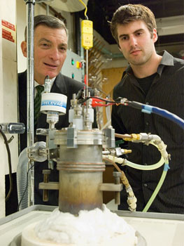 Professor Donald Sadoway and graduate student David Bradwell observe one of their small test batteries in the lab