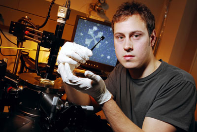 Graduate student Kevin Brenner holds a fabricated graphene sample