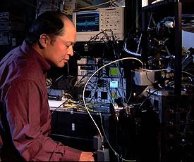 NIST physicist Sae Woo Nam works with refrigeration equipment used to cool photon detectors to nearly absolute zero. His team�s efforts have created devices that can detect single photons with 99 percent efficiency