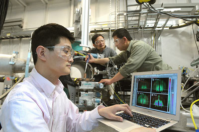 Assistant physicist Zhang Jiang (from left) examines a X-ray diffraction as physicist Jin Wang and nanoscientist Xiao-Min Lin prepare a sample at one of the Advanced Photon Source's beamlines