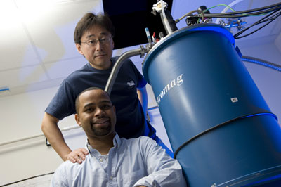 Rice University Professor Junichiro Kono, standing, and graduate student Thomas Searles set out to study interactions between magnetic fields and electrically charged particles and found that strong magnets can stop the flow of electrons through metallic single-walled carbon nanotubes