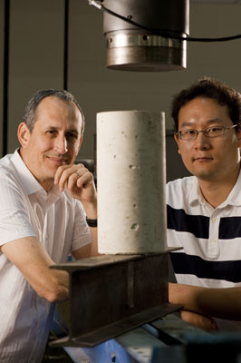 Scientists Pedro Alvarez (left) and Jaesang Lee stand behind a concrete cylinder and an I-beam, which is among the construction materials that manufacturers could potentially improve using certain nanomaterials.