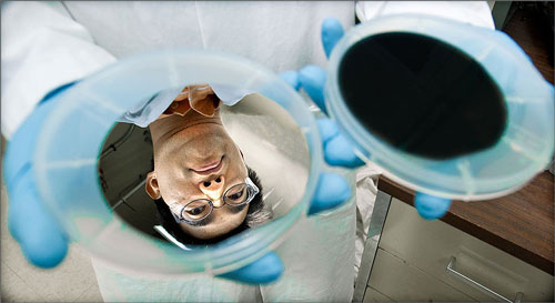 A silver wafer reflects the face of NREL research scientist Hao-Chih Yuan