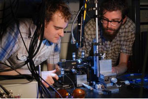 Research physicists Jonathan Matthews (left) and Kostas Poulios aligning the quantum optical chip. The photons are injected into the chip using optical fiber and requires precision alignment.