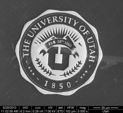 This electron microscope image shows a gilded University of Utah medallion