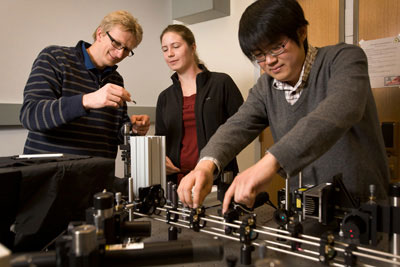 Ulrich Wiesner, left, works with graduate students Jennifer Drewes and Kai Ma to characterize the size and brightness of C dots