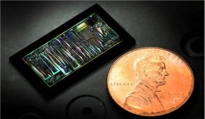 This is a dark-field optical image of a silicon photonic chip is shown in comparison to the size of a penny.
