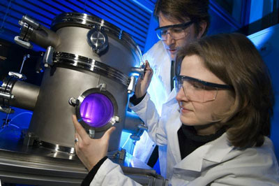 Scientists working with a plasma chamber