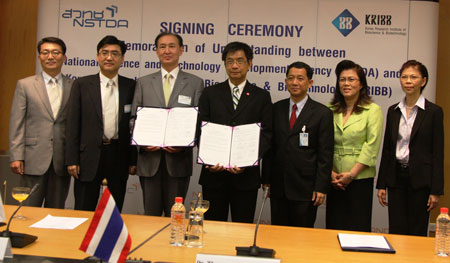Dr. Choe (left) and Dr. Thaweesak holding the signed MOU