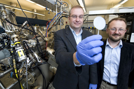 Purdue professors Michael Manfra, from left, and Gabor Csathy stand next to the high-mobility gallium-arsenide molecular beam epitaxy system at the Birck Nanotechnology Center