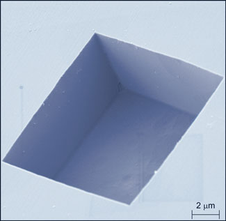 colorized electron microscope image reveals the boxy shape of the pits etched into the diamond surface
