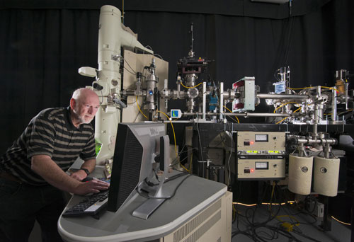 Daniel Buller stands in front of the beamline that connects the tandem accelerator to the transmission electron microscope (TEM) at Sandia's Ion Beam Laboratory