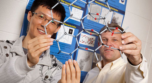 Physics Professor Michael Weinert and engineering graduate student Haihui Pu display the atomic structure on graphene monoxide