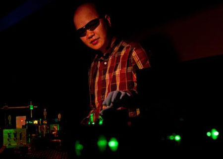 Cuong Dang manipulates a green beam that pumps the nanocrystals with energy, in this case producing red laser light