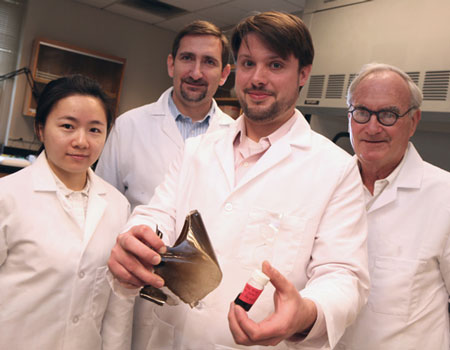 Post-doctoral chemist Jaeton Glover (center) displays samples of polymers reinforced with graphene oxide