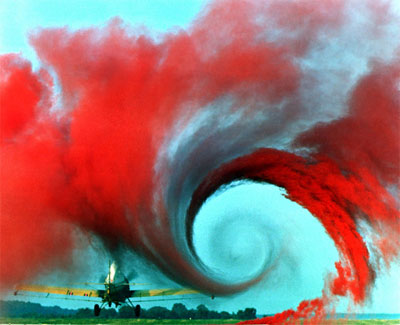 aerodynamics vortex with twisting red smoke produced by a rotating airplane