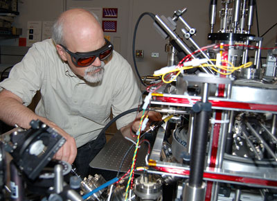 NIST researcher Jabez McClelland makes adjustments on the new magneto-optical trap ion source