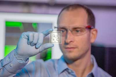 researcher looking at lab-on-chip device