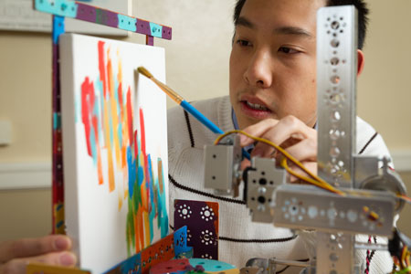 Wake Forest sophomore Tim Lee demonstrates the robot arm that he has programmed to paint pictures