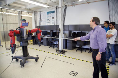 Alan Wagner, assistant professor of aerospace engineering, conducts an experiment with a Baxter robot in the Robot Ethics and Aerial Vehicles Lab